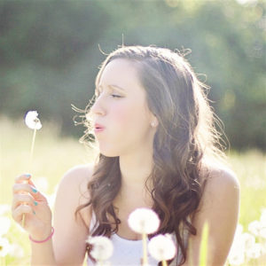 Woman blowing on a dandelion creating an auditory trigger