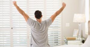 Man wakes up early and stretches before starting his day